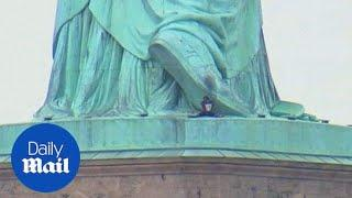 Female protestor climbs the Statue of Liberty on Independence Day - Daily Mail