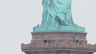 Woman climbs Statue of Liberty to protest family separations