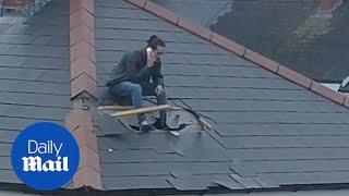 Man bursts out of his house roof as police break down his door